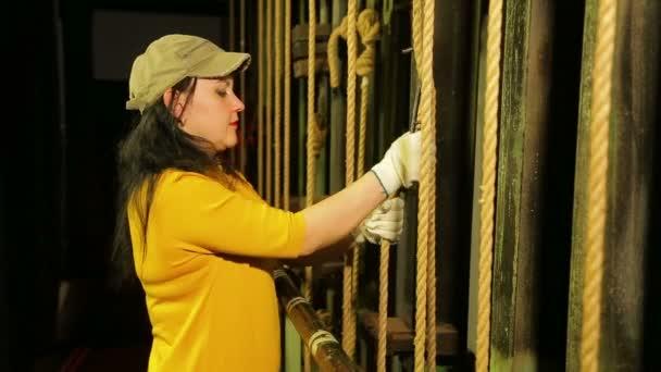 Egy fiatal női színpadi munkás kesztyű eltávolítja a Mount egy kábelemelő mechanizmusa színházi függöny, és felemeli.