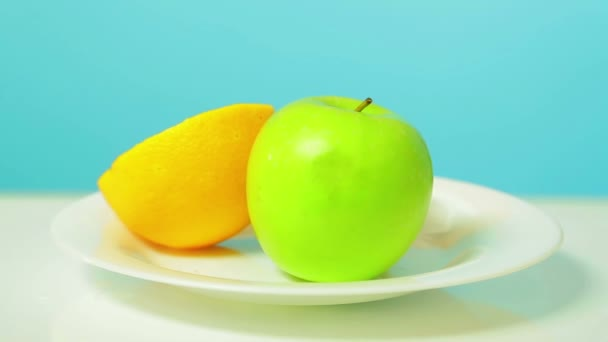 Whole green apple half of kiwi and orange on a white plate rotates in a circle