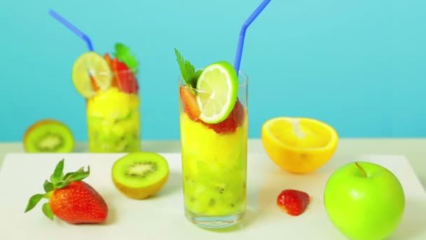 Fruit cocktail in a glass decorated with lime with a blue straw on a blue background. Near kiwi, strawberry, apple. Glass rotates in a circle