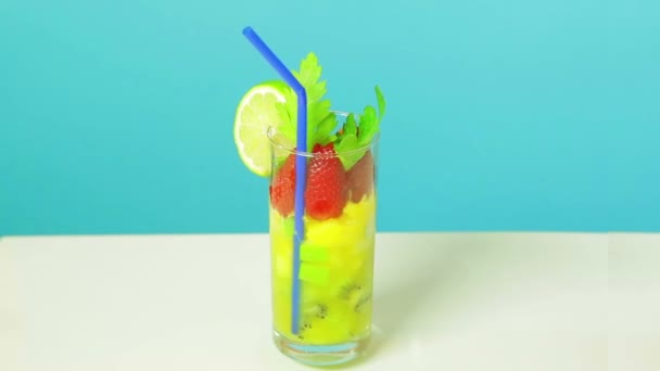 Fruit cocktail in a glass of kiwi, apple and strawberry slices decorated with lime with a blue straw on a blue background. Glass rotates in a circle