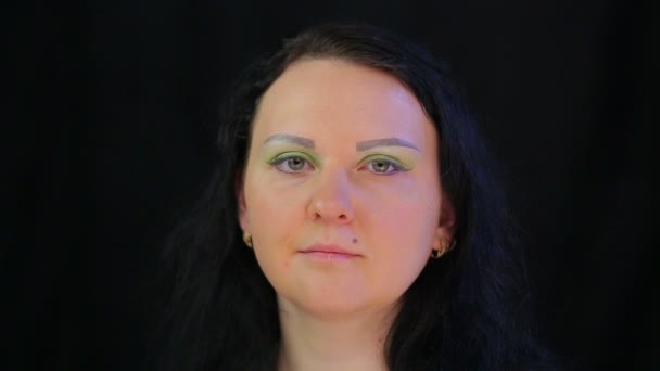 A brunette womans face with eye makeup with bright green shadows
