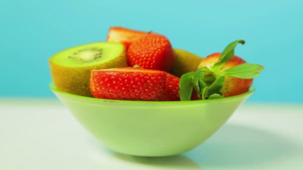 Fresh fruit of kiwi and sliced strawberries on a blue background on a green plate rotates in a circle. Close-up