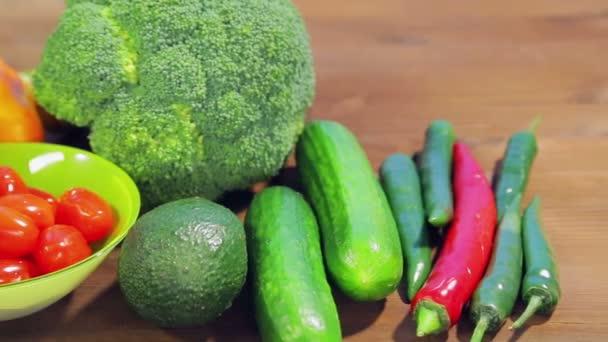 Na dřevěném stole jsou čerstvá zelenina cuketa, brokolice, hlávkový salát, avokáda, okurky, pepř a chilli papriky, třešňová rajčata