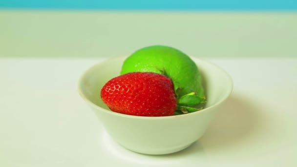 Lime fruit and ripe strawberries on a white plate rotates in a circle.