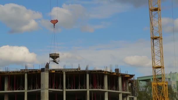 Věžové jeřáby vyvolávají a snižují materiál pro stavební práce na budově. Časové skoky