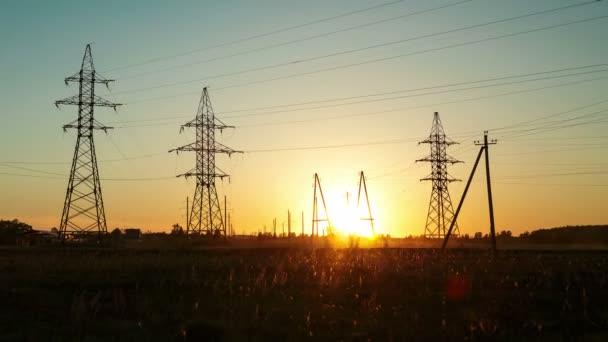 Sonnenuntergang auf dem Land vor dem Hintergrund von Hochspannungsleitungen. Zeitrunden