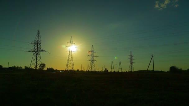 Běh mraků na pozadí vysokonapěťových linek na venkově při západu slunce. Časové skoky