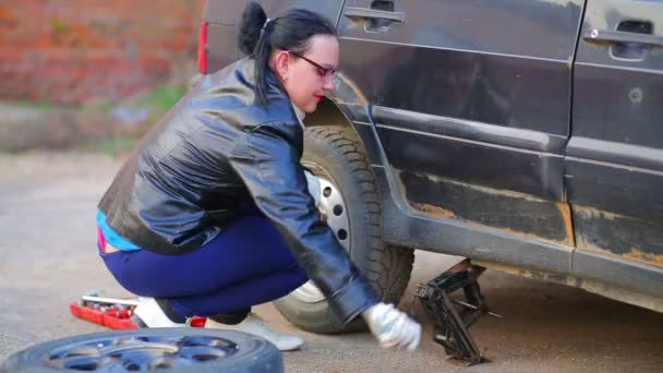 The woman sets the jack to lift the car.