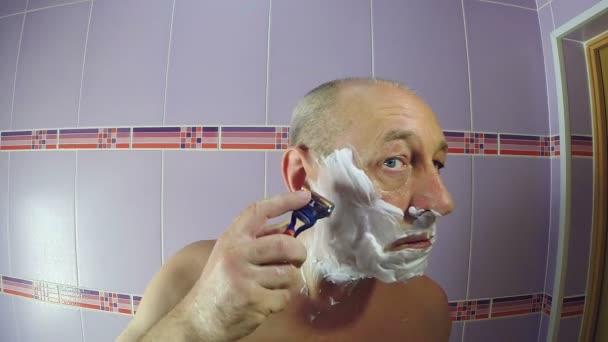 Muž v koupelně oholí strniště kolem spánků a břitvou.
