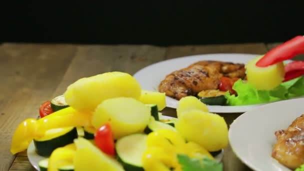 Female hand puts slices of vegetables in a plate with green salad and chicken.