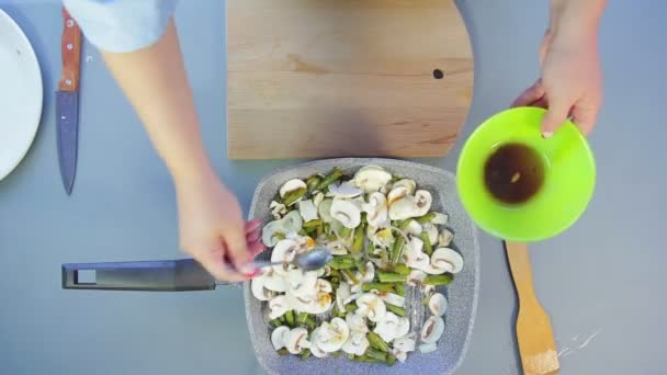 A woman mixes mushrooms and onions in a pan with a wooden spatula and adds soy sauce
