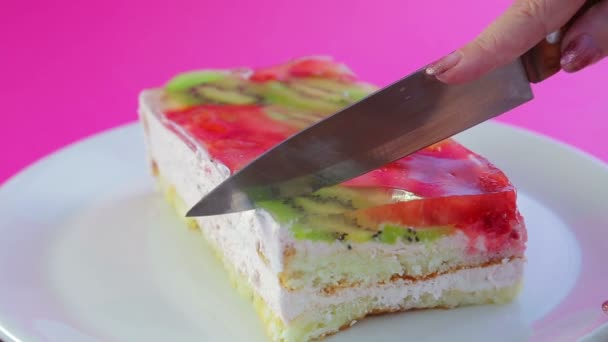Female hand holds knife and cuts fruit cake into pieces.