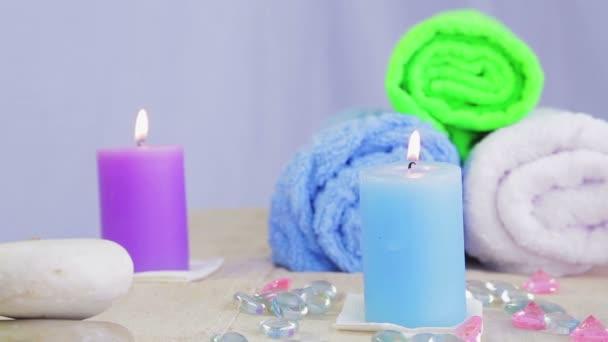 Stůl v lázeňském salonu se svíčkami, ručníky a kameny pro léčbu a relaxaci