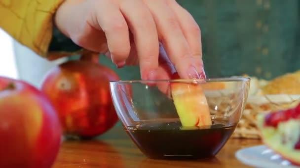 A női kéz vesz egy szelet egy almát, és mártogatós azt mézzel a nyaralás Ros hásáná