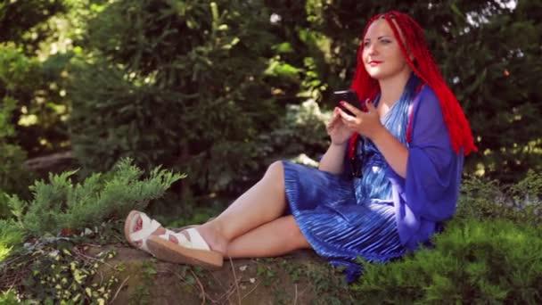 Mladá žena sedí na trávě v parku a komunikuje v poslíčku