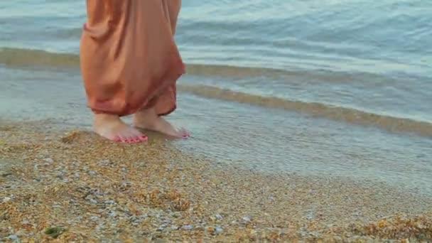 Női lábak széles nadrágban mezítláb megy végig a szélén a tengervíz