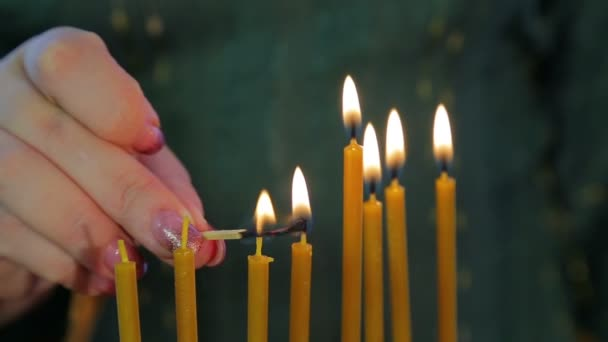 A female hand lights candles on Hanukkah in a beautiful candlestick.