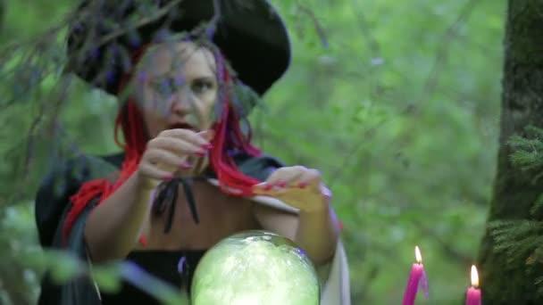 Čarodějka s červenými vlasy v lese kouzly se světélkující koulí a hořící svíčkami