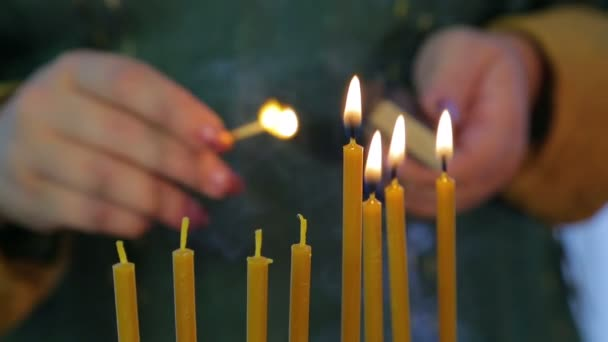 A female hand lights candles on Hanukkah in a beautiful candlestick