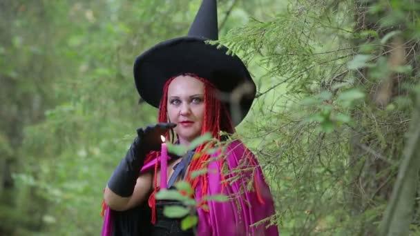 egy fiatal boszorkány, vörös hajú, hegyes kalapot, és egy fekete köpenyt varázsol gyertyákkal az erdőben
