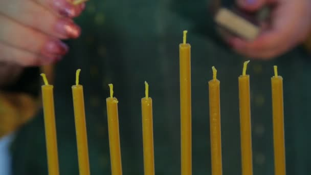 Female hand lights candles on Hanukkah time laps.