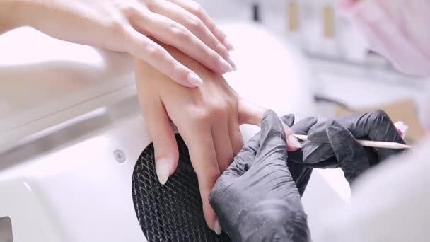 Žena manikérka s rukavicemi v salonu krásy odtlačí pokožku dřevěnou holí na nehty klienta před nanesením gelového povlaku.