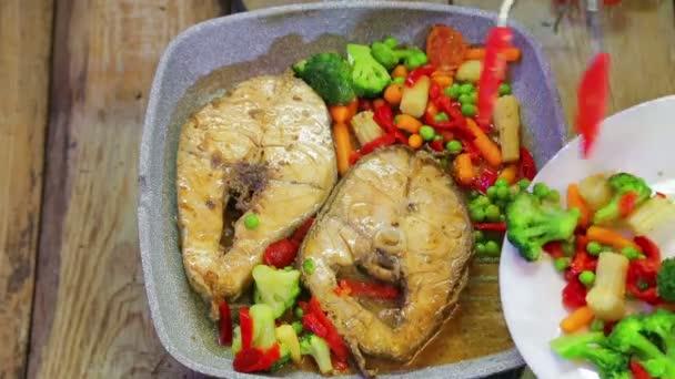 Žena vkládá čerstvou barevnou zeleninu do pánve s rybami.