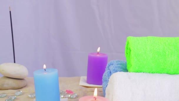 Lázeňský salon se svíčkami, ručníky a kameny pro terapii.