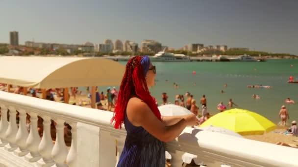 Na promenádě stojí mladá žena v šálu s africkými copánky a dívá se na moře a pláž.