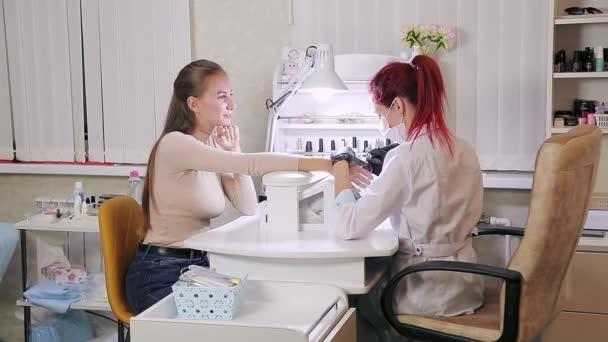 Žena manikérka s rukavicemi v salonu krásy dělá hardwarovou manikúru klientovi před nanesením gel povlak.