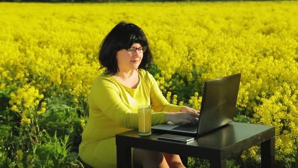 Egy sárga ruhás fiatal nő egy sárga mezőn egy napsütéses napon távolról dolgozik a számítógépnél.