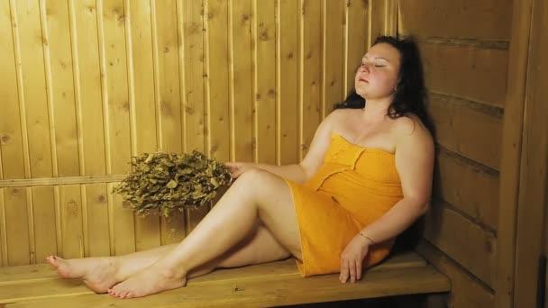 Eine junge brünette Frau sitzt in einer Badewanne mit einem in ein Handtuch gewickelten Besen.