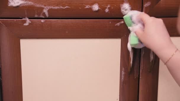 Samice ruční houba s čisticím prostředkem čistí kuchyňský nábytek