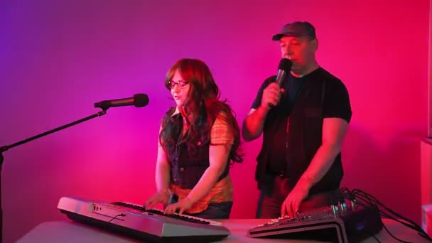 Muž a žena v nahrávacím studiu zpívají do mikrofonu. Hraje na syntezátor.