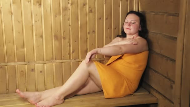 Junge brünette Frau in Badewanne schmiert Körpercreme, die in ein Handtuch gewickelt ist