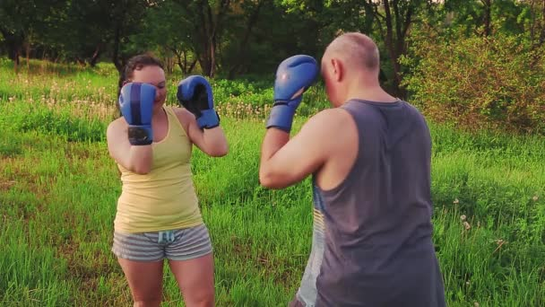 Man and woman in the morning in the park are training Thai boxing in gloves.