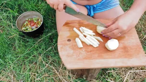 Woman cuts into potatoes for soup on a stump in nature
