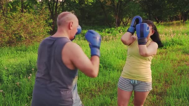 Man and woman in the park are training Thai boxing in gloves