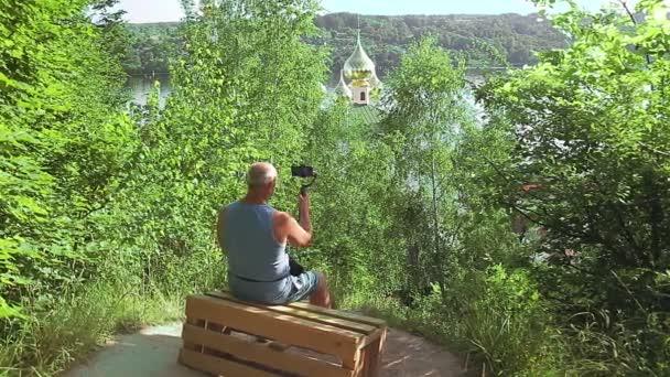Mužský blogger s mobilním telefonem o cestování mluví o chrámu zezadu.