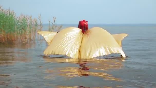 Egy nő fekete fűzőben démon alakjában, arany szárnyakkal a vízen sétál egy tóban, szárnyaival a háta mögött..