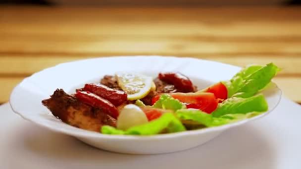 Bílý talíř s kousky masa grilovanými na listech salátu s kečupem a citrónem a třešní se otáčí v kruhu.