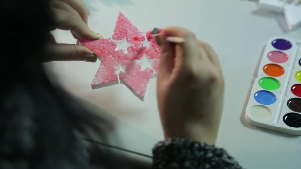 Womans hands on a winter evening makes home decorations for Christmas by painting figures with watercolors