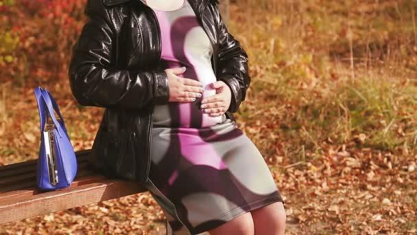 Těhotná žena fotí bez tváře v uličce na lavičce a hladí si břicho