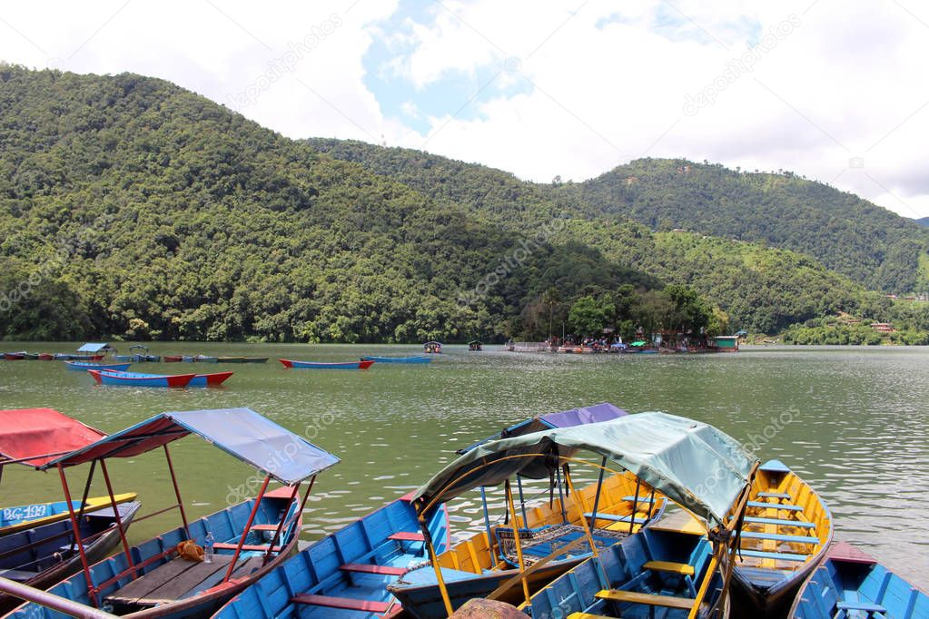 Boats around Phewa Lake and hills in Pokhara, a popular tourist destination. Taken in Nepal, August 2018.