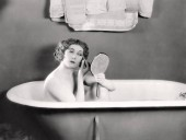 Naked woman putting on her makeup in the bathtub