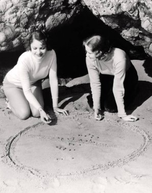 Two women playing a game of marbles in a circle in the sand
