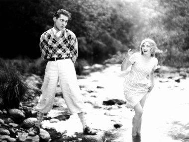Woman coaxing man into a stream