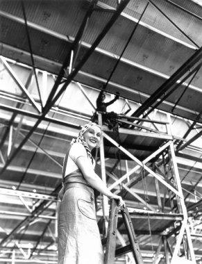 Woman climbing a ladder on a construction site