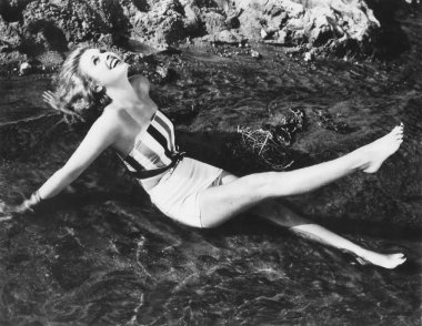 Young woman sunning herself in the ocean
