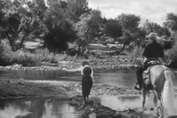 Woman crossing stream with cowboy on horseback, 1930s